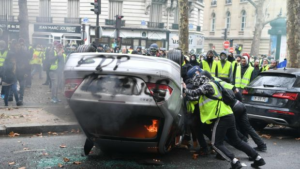 Demonstrators destroy a car during a protest of yellow vests against rising oil prices in Paris: Photograph: Getty