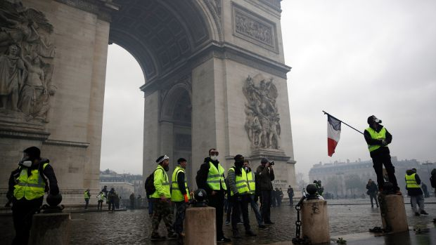 Protesters wearing yellow vests occupy the Place de l'Etoile at the foot of the Arc de Triomphe, as they clash with riot police. Photograph: EPA