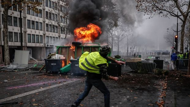 Protesters wearing yellow vests clash with riot police near a burning barricade during a demonstration over high fuel prices on the Champs Elysee in Paris on Saturday. Photograph: EPA