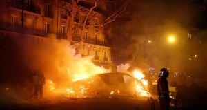 Firemen extinguish burning cars set alight by protesters wearing yellow vests, during clashes near the Place de l'Etoile in Paris, France. Stephane Mahe/Reuters
