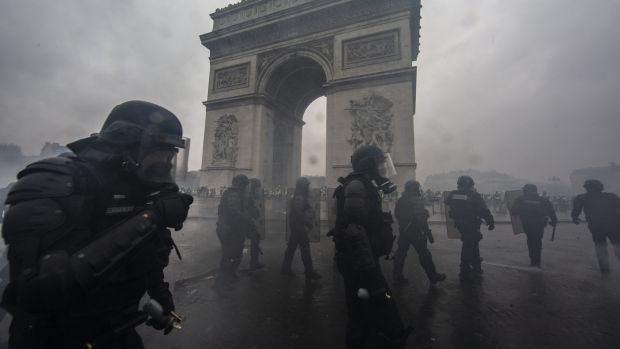 Teargas surrounds riot police as they clash with protesters during a 'yellow vest' demonstration near the Arc de Triomphe. Photograph: Getty