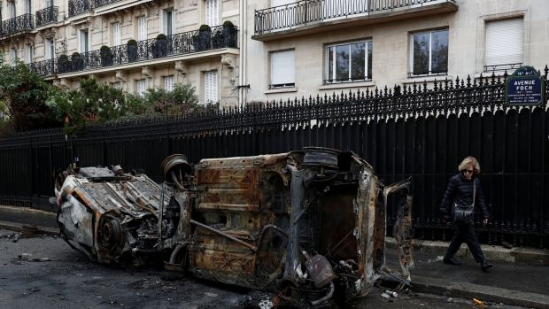 Burned-out, upturned cars on Avenue Foch on Sunday morning after clashes with protesters wearing yellow vests, in Paris, France. Photograph: Reuters