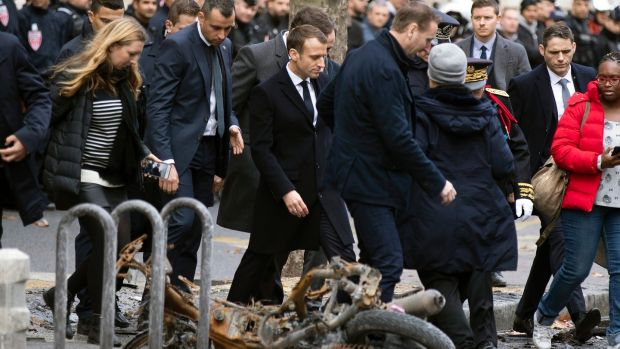 French president Emmanuel Macron (centre) on Sunday assesses the damage from the 'yellow vests' protests next to the Champs Elysee in Paris. Photograph: EPA