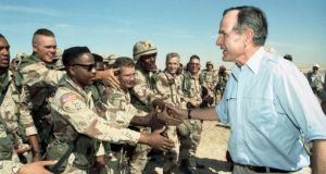President George HW Bush greets American troops in Saudi Arabia weeks before the start of the Persian Gulf war in 1991. File photograph: George Bush Presidential Library/New York Times