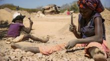 A child and a woman break rocks at a cobalt pit in Lubumbashi in the DRC. Photograph: Junior Kannah/AFP/Getty Images