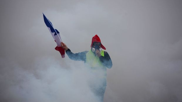 "A demonstrator holds up a furled French flag amid billowing tear gas during a ""gilets jaunes"" (yellow vests) protest against rising oil prices and living costs in Paris. Photograph: AFP/Getty Images"