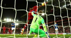 Divock Origi of Liverpool scores a strange goal past Jordan Pickford of Everton. Photograph: Clive Brunskill/Getty Images