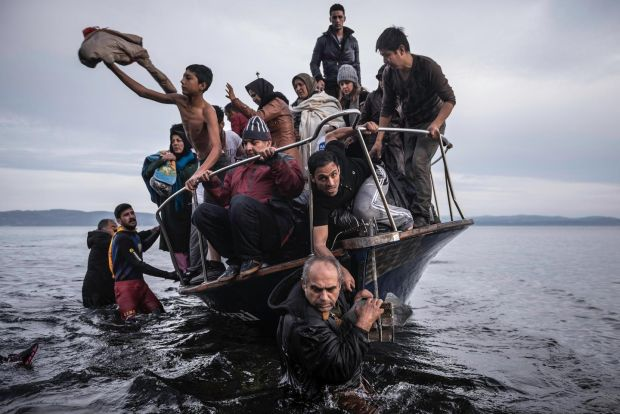 Migrants make land on a Turkish boat close to the village of Skala, on the Greek island of Lesbos on November 16th, 2015 Photograph: Sergey Ponomarev