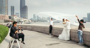 Chinese models pose for a wedding picture in Shanghai on Bund's promenade. The state is frowning on fancy celebrations.