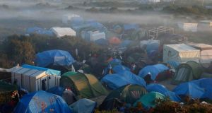 Fog hangs above tents and makeshift shelters in  a field where migrants and asylum seekers stay in Calais, France, October 2nd 2015.   Most of the unaccompanied minors arrived in Ireland from Calais or Greece Photograph: Pascal Rossigno/Reuters