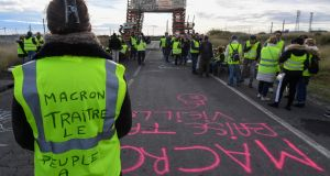 A yellow vests (gilets jaunes) protester with the words written of the back of her vest that read, ' Macron traitor, the people are hungry' blocks the road leading to the Frontignan oil depot in the south of France, as they demonstrate against the rise in fuel prices and the cost of living Photo: Pascal Guyot / AFP