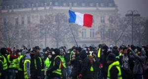 "Demonstrators near the Arc de Triomphe during a protest of ""yellow vests"" against rising fuel prices and living costs in Paris on Saturday. Photograph:  AFP/Getty Images"