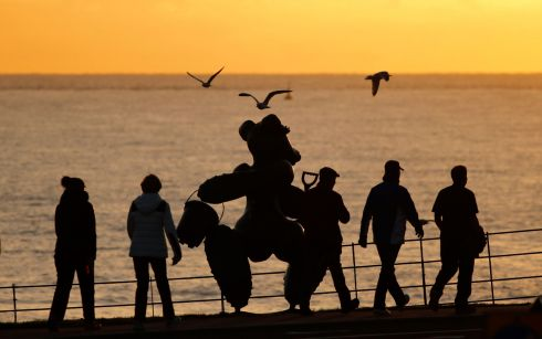 Early morning light and walkers on Greystones seafront passing the bronze teddy bear sculpture by Partick O'Reilly, which was commissioned in memory of Caroline Dwyer Hickey. Photograph: Nick Bradshaw