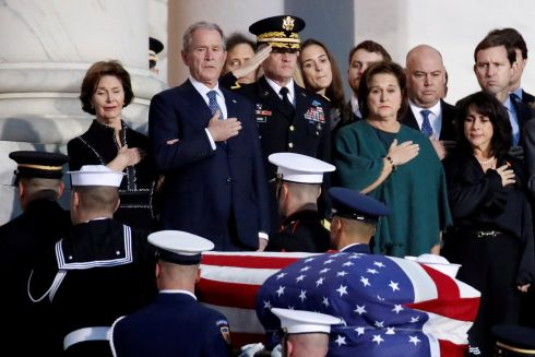 Former US president George W Bush and other family members watch as the flag-draped casket of former president George HW Bush is carried by a guard of honour to lie in state in the rotunda of the US Capitol, in Washington. Photograph: Alex Brandon