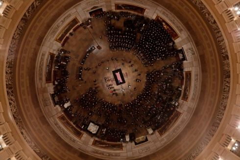 People begin to fill out out as former US president George HW Bush lies in state in the Rotunda, Washington DC. Photograph: Morry Gash