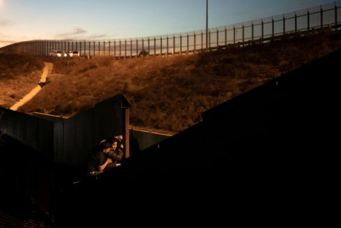 Migrants, part of a caravan of thousands from Central America trying to reach the United States, climb a border fence as they try to cross illegally from Mexico to the US, in Tijuana, Mexico. Photograph: Alkis Konstantinidis/Reuters