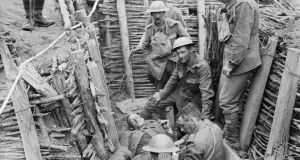 Irish Guardsmen attend to a wounded German, on July 31st, 1917. Liam O'Flaherty served in this regiment. Photograph: Lt. Ernest Brooks/ IWM via Getty Images