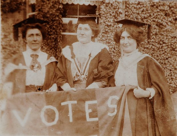 "Hanna Sheehy-Skeffington, Kathleen Shannon and Kate Sheedy, in their graduation robes and mortar-boards, carrying a banner saying ""Votes"" (for women)