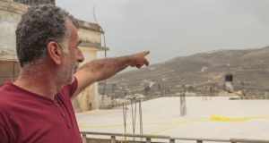 Akram Abu Kareem, olive farmer in Burin, points towards his olive trees, which are adjacent to an Israeli settlement. Photograph: Niall Sargent