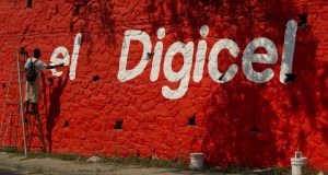 Workers paint the Digicel brand on a wall in Haiti. Digicel operates in 31 markets in the Caribbean, Central America and the Asia-Pacific region. Photograph: Ken Cedeno/Digital/Corbis via Getty Images