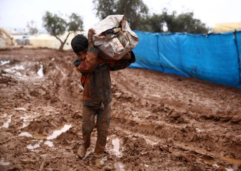 CAMP: A Syrian boy carries a sack on his shoulder while walking in the mud at a camp for the displaced near the village of Shamarin, near the border with Turkey in the northern Aleppo province on December 6th. Photograph: Nazeer Al-Khatib/AFP/Getty Images