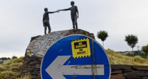 "A sticker reading ""No Border, No Brexit"" on a road sign near the Hands Across the Divide sculpture in Derry. Photograph: Mary Turner/Bloomberg"