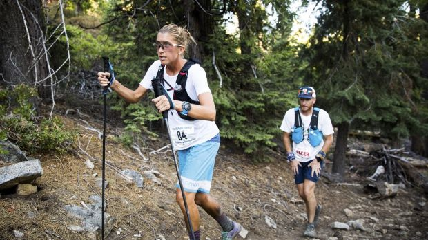 Courtney Dewaulter hikes uphill with her pacer Mike Wilkinson at about 155 miles into the Tahoe 200 ultramarathon in Strawberry, California.