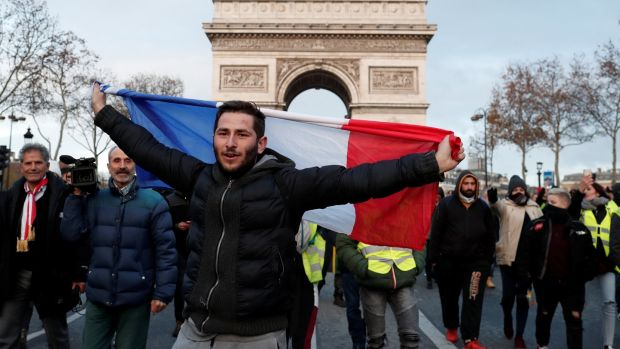 A protester holds the French flag as he walks with others wearing yellow vests. Photograph: Benoit Tessier/Reuters