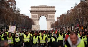 Protesters wearing yellow vests take part in a demonstration below the Arc de Triomphe in Paris. Photograph: Benoit Tessier/Reuters