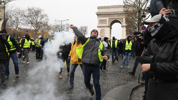 A demonstrator throws a tear gas canister during the demonstration of the yellow vests at the Arc de Triomphe. Photograph: Jeff J Mitchell/Getty Images
