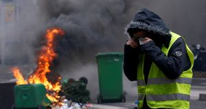 A protester stands next to burning rubbish bins during clashes with police at a national day of protest by the 'yellow vests' movement in Paris on December 8th. Photograph: REUTERS/Stephane Mahe TPX