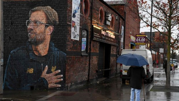 "A woman walks past a recently created mural of Liverpool's German manager Jurgen Klopp by street artist ""Akse"" in Liverpool. Photo: Paul Ellis/Getty Images"
