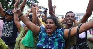 Supporters of Sri Lanka's ousted prime minister, Ranil Wickremesinghe, celebrate outside the supreme court  in Colombo on Thursday after it ruled the president's dissolution of parliament was illegal. Photograph: Reuters