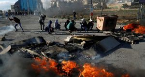 Palestinians take cover during clashes with Israeli troops in the Israeli-occupied West Bank. Photograph: Mohamad Torokman/Reuters