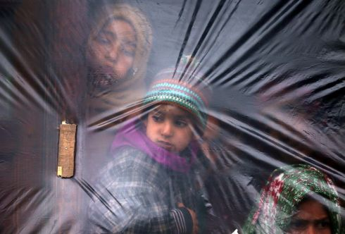 INDIA: Children look out from a window, covered with a plastic sheet to protect from cold, on a winter day in a village of south Kashmir's Pulwama district. Photograph: Danish Ismail/Reuters