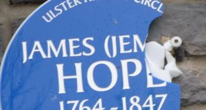Damaged Ulster History Circle plaque at Mallusk Cemetery in memory of United Irishman James (Jemmy) Hope