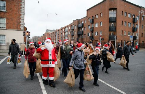 GOOD TIDINGS: Santa and students make their way through Dublin's north inner city with gift sacks for residents at a homeless facility on Sean McDermott Street. Photograph: Nick Bradshaw/The Irish Times
