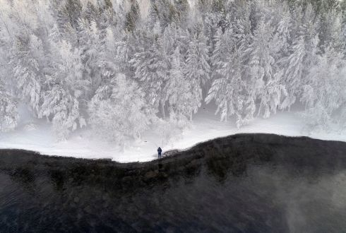 FREEZING POINT: A man fishes on a bank of the Yenisei river while it is covered with snow and hoarfrost, outside the Siberian city of Krasnoyarsk, Russia. Photograph: Ilya Naymushin/Reuters