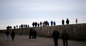 ON THE MARCH: Walkers on the pier in Howth, Co Dublin. Photograph: Nick Bradshaw for The Irish Times