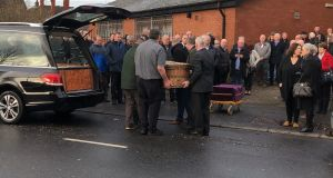 Mary Garland (right) looks on as the casket of her husband, former Workers' Party chief  Seán Garland, is taken from a hearse at the Lower Falls Social Club, Belfast. Photograph: Michael McHugh/PA Wire.