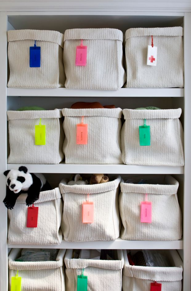 White woven storage baskets with individual labels for organizing a child's bedroom