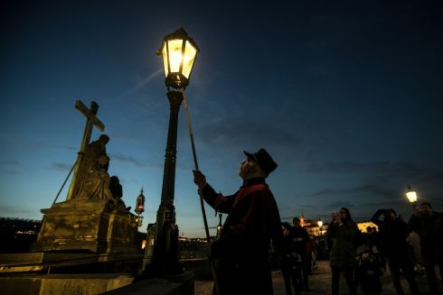 LIGHTING UP: Jan Tater lights a historic gas lamp on Charles Bridge in Prague, Czech Republic. Every day at dusk at this time of year, the lamglighters spark up 37 historic gas lamps on the medieval bridge as an attraction for tourists. The first gas lamps were installed on the bridge in 1848.  Photograph: Martin Divisek/EPA