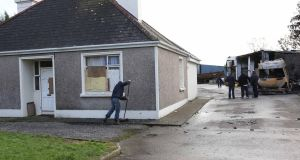 Friends and neighbours help clean up the debris at  the   house in Strokestown, Co Roscommon, which was the centre of an eviction last week.  Photograph: Brian Farrell