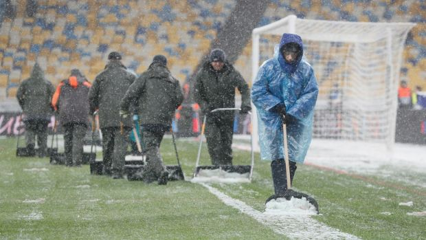 Workers clear snow from the pitch in Kyiv before the match. Photo: Sergey Dolzhenko/Getty Images