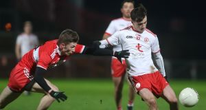 Tyrone's Darragh Canavan scores a point despite the attempt of Derry's Paul McNeill to block him. Photograph: Lorcan Doherty/Inpho