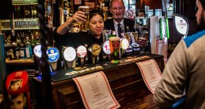 Staff and a customer are pictured in the Long Stone on Townsend Street in Dublin on Friday. Photograph: James Forde/The  Irish Times.