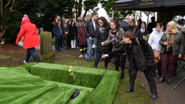 People toss flowers into Margaret Lang's grave at her funeral in Trim, Co Meath on Thursday. Photograph: Alan Betson/The Irish Times