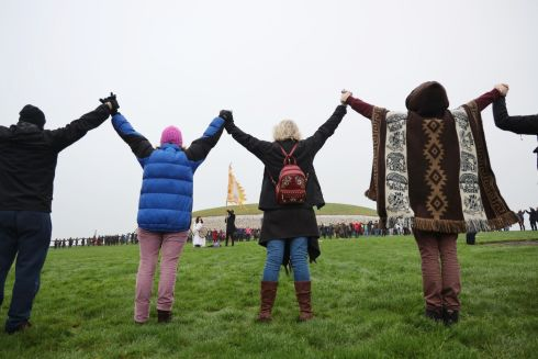 DAWN CHORUS: A large circle of people hold hands and chant at Newgrange at dawn on the winter solstice. Photograph: Alan Betson/The Irish Times