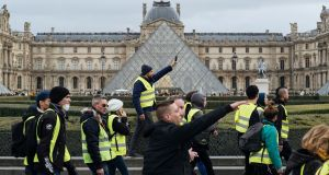 'Yellow vest' protesters  walk past the Louvre  in Paris, France, on Saturday. Photograph: AP Photo/Kamil Zihnioglu