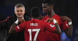 Manchester United caretaker manager Ole Gunnar Solskjaer celebrates with Fred and Paul Pogba after their victory over Cardiff. Photograph: Stu Forster/Getty Images